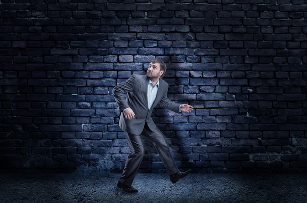 Bang zakenvrouw staande tegen een zwarte muur