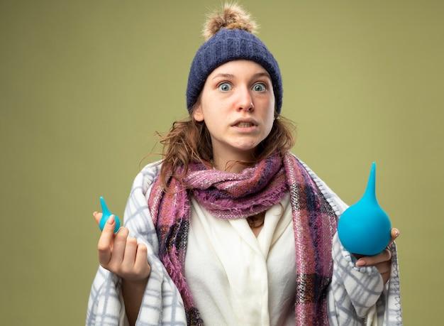 Bang ziek meisje dragen witte mantel en winter hoed met sjaal verpakt in plaid bedrijf klysma's geïsoleerd op olijfgroen