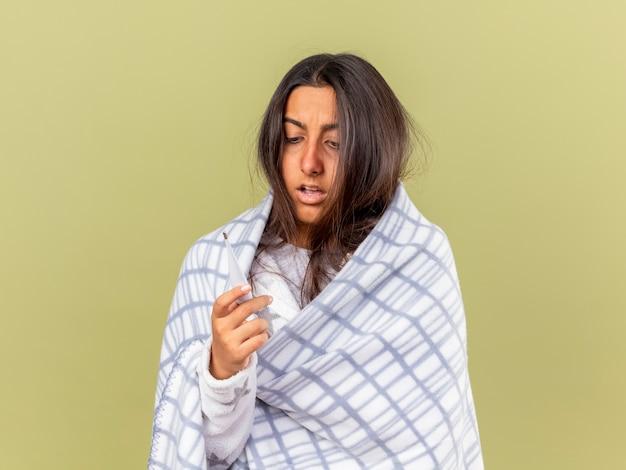 Bang ziek meisje gewikkeld in geruite bedrijf en kijken naar thermometer geïsoleerd op olijfgroene achtergrond