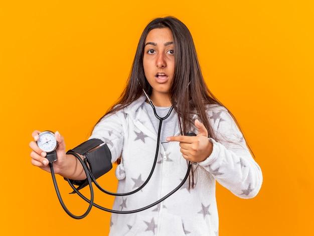 Bang ziek meisje haar eigen druk meten met bloeddrukmeter geïsoleerd op gele achtergrond