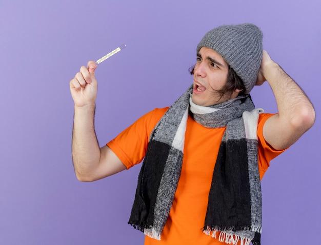 Bang zieke jongeman dragen winter hoed met sjaal houden en kijken naar thermometer hand zetten haed geïsoleerd op paarse achtergrond