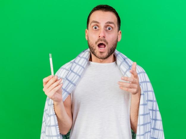 Bang zieke jongeman gewikkeld in plaid en thermometer geïsoleerd op groene achtergrond te houden