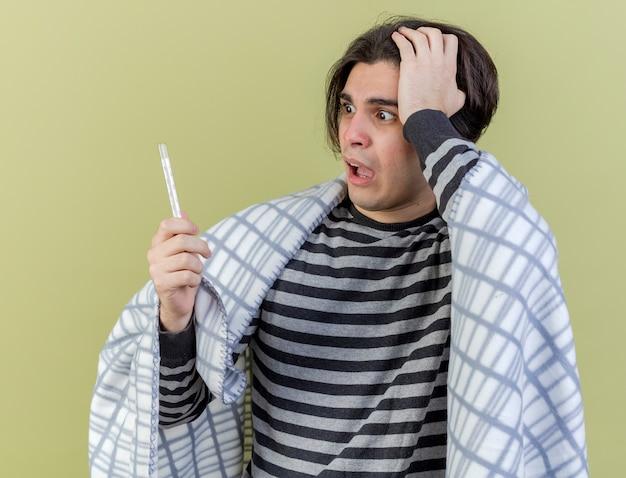 Bang zieke jongeman verpakt in geruite bedrijf en kijken naar thermometer hand op hoofd geïsoleerd op olijfgroene achtergrond te kijken