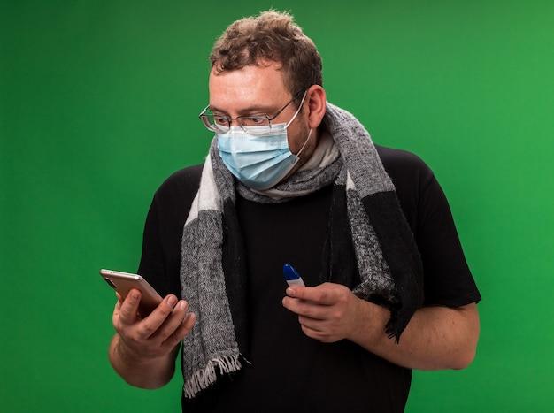 Bang zieke man van middelbare leeftijd met medisch masker en sjaal met thermometer en kijkend naar telefoon in zijn hand geïsoleerd op groene muur