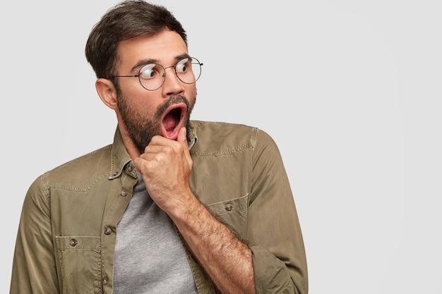 Bange, angstige man houdt de hand bij geopende mond, kijkt met een zeer angstige uitdrukking opzij, merkt iets vreselijks op, draagt een ronde bril en een modieus shirt, poseert tegen een witte muur