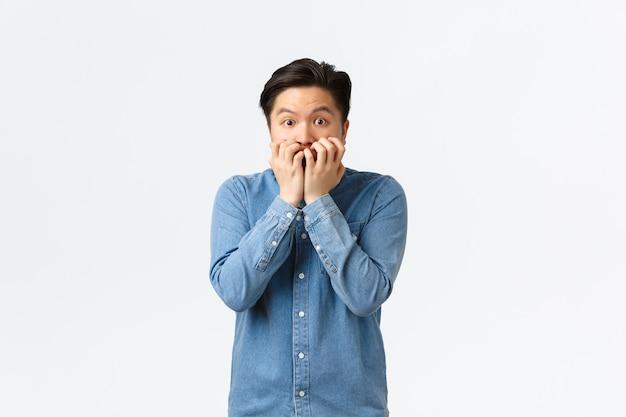 Bange aziatische man die rilt van angst en vingernagels bijt, bang en onzeker naar de camera kijkt. bange man in paniek staart angstig, is getuige van een vreselijk ongeluk, kijkt naar horrorfilm.