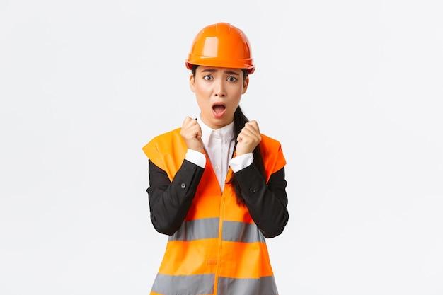 Bange aziatische vrouwelijke ingenieur in paniek die geschokt en bang kijkt, rillend van angst, veiligheidshelm en reflecterend jack draagt, bezorgd en gealarmeerd omdat hij een probleem heeft in de bouwzone