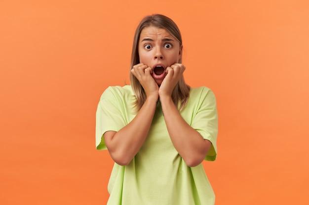 Bange, bange jonge vrouw in gele t-shirt houdt handen op de wangen en kijkt bang geïsoleerd over oranje muur