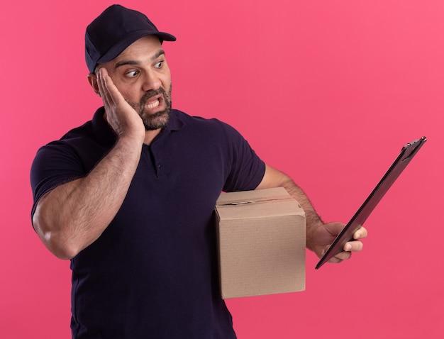 Bange bezorger van middelbare leeftijd in uniform en pet met doos die naar klembord in zijn hand kijkt geïsoleerd op roze muur