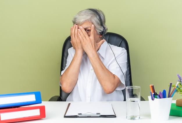 Bange blanke vrouwelijke callcenter-operator op koptelefoon zittend aan bureau met kantoorhulpmiddelen die haar gezicht bedekken met handen door vingers geïsoleerd op groene muur