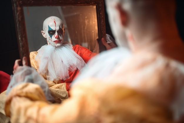 Bange bloedige clown die in de spiegel kijkt