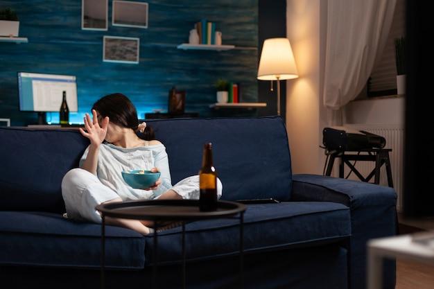 Bange doodsbange vrouw kijkt naar horrorfilm op televisie die popcorn eet