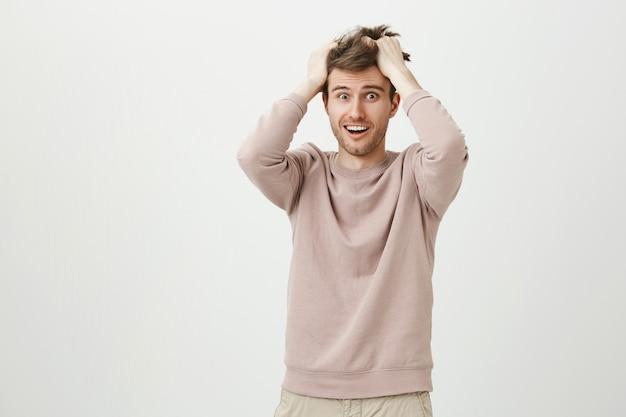 Bange en angstige man die haar haren aan het gooien is en gealarmeerd kijkt