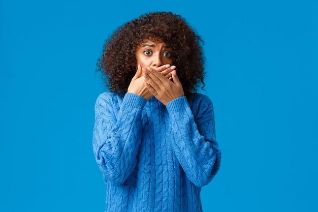 Bange en timide, onzekere, angstige jonge afro-amerikaanse vrouw is getuige van een vreselijk tafereel
