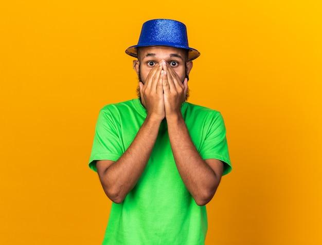 Bange jonge afro-amerikaanse man met een feestmuts bedekt gezicht met handen