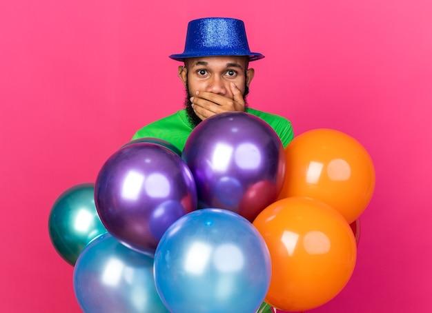 Bange jonge afro-amerikaanse man met een feestmuts die achter ballonnen staat en zijn mond bedekt met hand