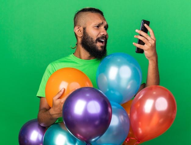 Bange jonge afro-amerikaanse man met een groen t-shirt die achter ballonnen staat en naar de telefoon kijkt