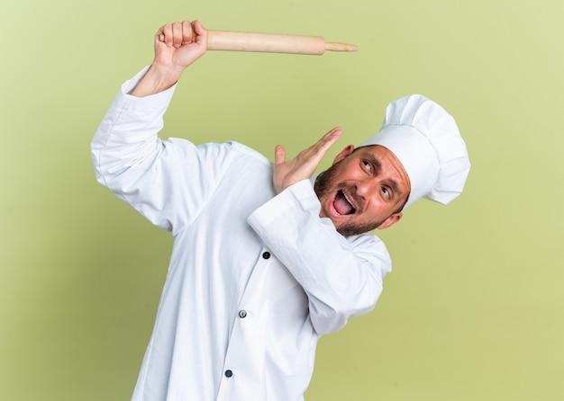 Bange jonge blanke mannelijke kok in chef-kokuniform en dop die deegroller opheft en opkijkt met weigeringsgebaar