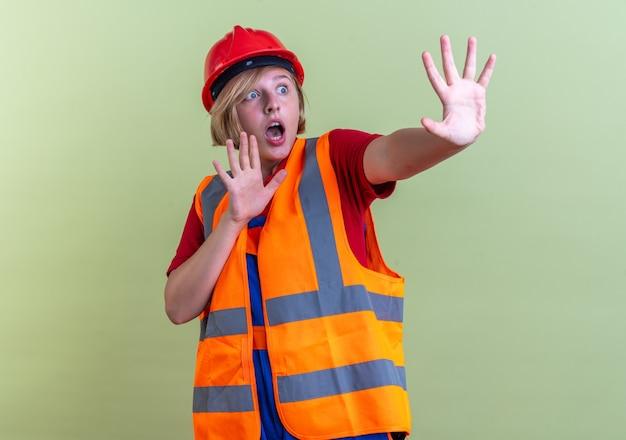 Bange jonge bouwvrouw in uniform die handen uitsteekt aan de zijkant geïsoleerd op olijfgroene muur