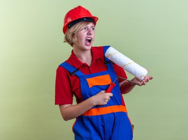 Bange jonge bouwvrouw in uniform met rolborstel geïsoleerd op olijfgroene muur