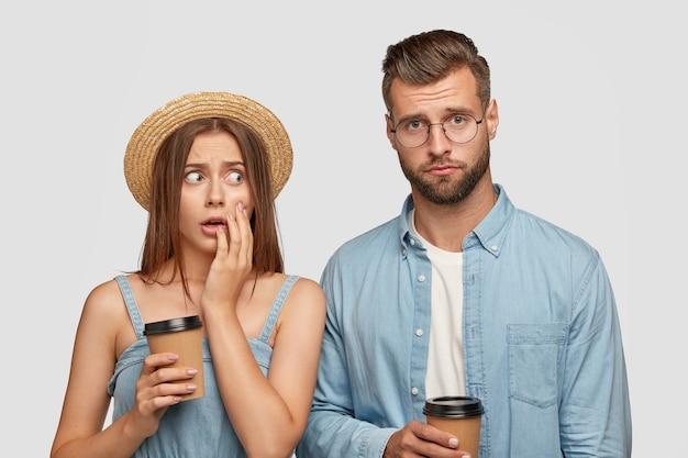 Bange jonge europese vrouw in strooien hoofddeksel kijkt angstig naar zijn metgezel die gefrustreerd gelaatstrekken