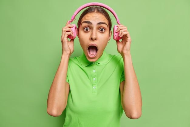 Bange jonge europese vrouw zet stereokoptelefoon uit staart afgeluisterde ogen wijd geopende mond kan niet geloven in schokkend nieuws terloops gekleed geïsoleerd over levendige groene muur