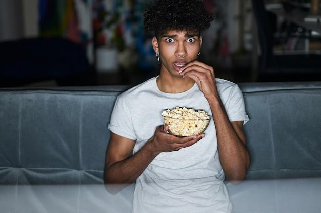 Bange jonge kerel met wijd open ogen in een pyjama die popcorn eet terwijl hij naar een horrorfilm kijkt
