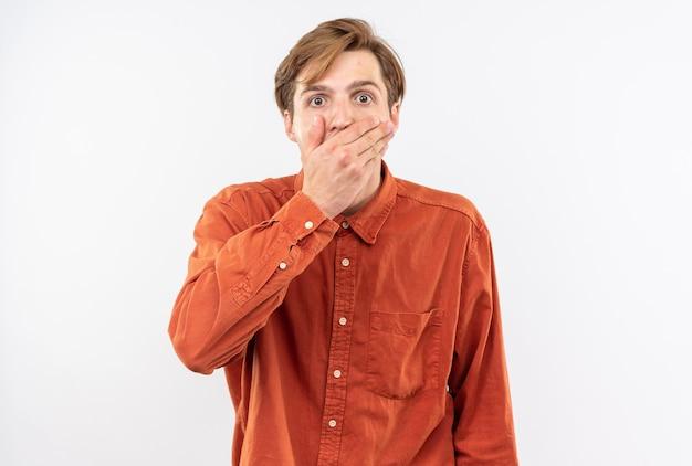 Bange jonge knappe kerel met een rood hemd bedekte mond met hand