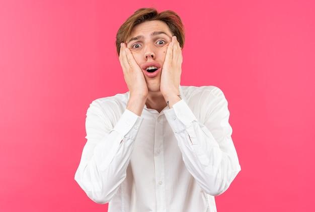 Bange jonge knappe kerel met een wit overhemd bedekt gezicht met handen geïsoleerd op een roze muur
