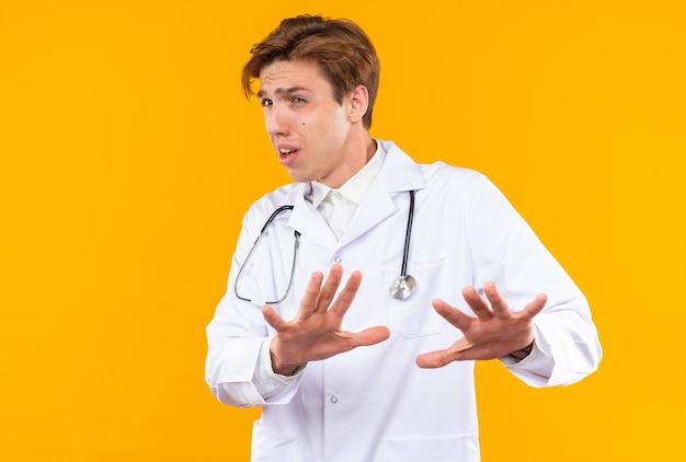 Bange jonge mannelijke arts die een medisch gewaad draagt met een stethoscoop die een stopgebaar toont