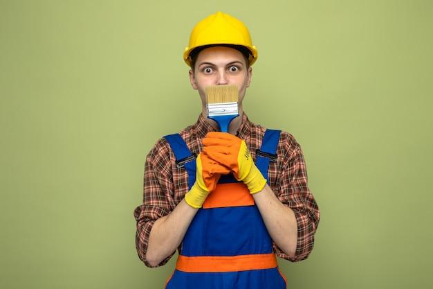 Bange jonge mannelijke bouwer die uniform draagt met handschoenen vast en bedekt gezicht met kwast