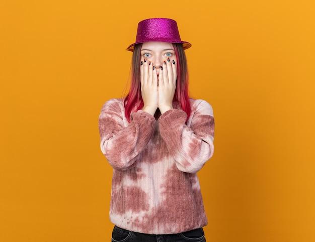 Bange jonge mooie vrouw met een feestmuts bedekt gezicht met handen geïsoleerd op een oranje muur