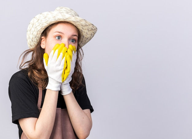 Bange jonge tuinman met een tuinhoed met handschoenen bedekt gezicht met handen geïsoleerd op een witte muur met kopieerruimte