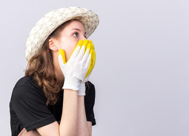 Bange jonge tuinman met tuinhoed met handschoenen bedekt gezicht met handen
