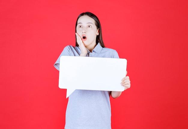 Bange jonge vrouw die een bord vasthoudt en haar hand voor haar mond houdt