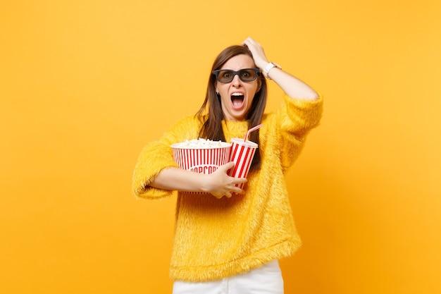Bange jonge vrouw in 3d imax-bril die zich aan het hoofd vastklampt, film kijkt, popcorn, kopje cola of frisdrank vasthoudt geïsoleerd op gele achtergrond. mensen oprechte emoties in de bioscoop, levensstijl.