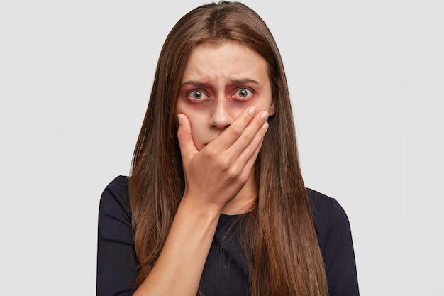 Bange jonge vrouw met blauwe plekken die zich voordeed tegen de witte muur
