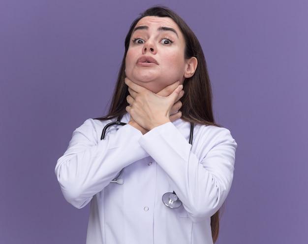 Bange jonge vrouwelijke arts die een medisch gewaad met een stethoscoop draagt, doet alsof ze zichzelf stikt met handen geïsoleerd op een paarse muur met kopieerruimte