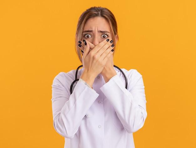 Bange jonge vrouwelijke arts met een medisch gewaad met een stethoscoop bedekt gezicht met handen geïsoleerd op een gele muur