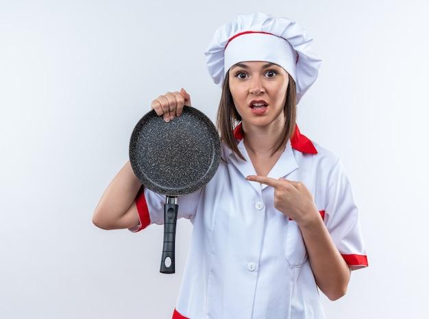 Bange jonge vrouwelijke kok die een uniform van de chef-kok draagt en naar een koekenpan wijst die op een witte muur wordt geïsoleerd