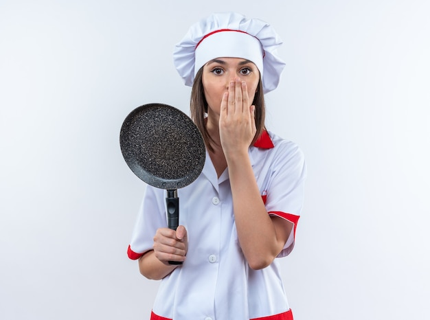 Bange jonge vrouwelijke kok in uniform van de chef-kok die een pan bedekt gezicht houdt met de hand geïsoleerd op een witte achtergrond