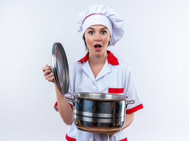 Bange jonge vrouwelijke kok met een uniform van de chef-kok die een steelpan met deksel vasthoudt die op een witte achtergrond wordt geïsoleerd