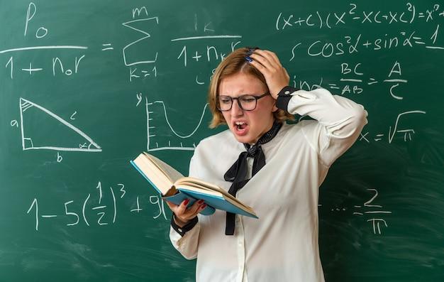 Bange jonge vrouwelijke leraar met een bril die voor het schoolbord staat en een boek leest dat de hand op het hoofd zet in de klas