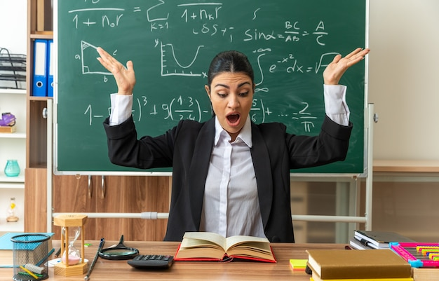 Bange jonge vrouwelijke leraar zit aan tafel met schoolbenodigdheden die een boek leest en handen uitspreidt in de klas