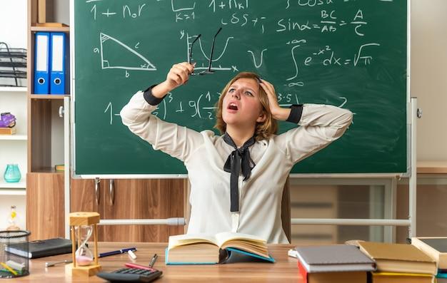 Bange jonge vrouwelijke leraar zit aan tafel met schoolbenodigdheden die een bril vasthoudt en kijkt en hand op het hoofd zet in de klas