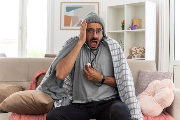 Bange jonge zieke man met optische bril gewikkeld in een plaid met een wintermuts die zijn hartslag meet met een stethoscoop en zijn hand op zijn gezicht legt zittend op de bank in de woonkamer