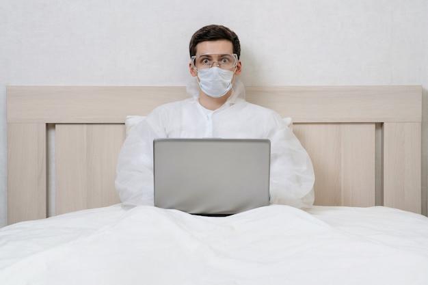 Bange jongeman in biologisch gevaarlijke kleding werkt op afstand met zijn laptop tijdens de quarantaine van het coronavirus.