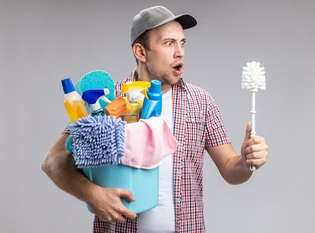 Bange jongeman met een dop die een emmer vasthoudt met schoonmaakgereedschap en naar een borstel in zijn hand kijkt die op een witte achtergrond wordt geïsoleerd