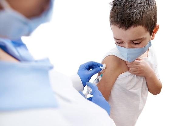 Bange jongen kijkt naar zijn hand terwijl de dokter hem vaccineert