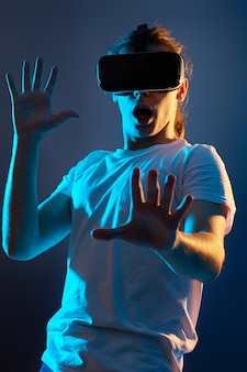 Bange man in een bril van virtual reality die videogames speelt op een donkerblauwe achtergrond. neonlicht.